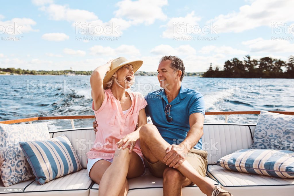 Living happily ever after out on a lake Shot of a mature couple enjoying a relaxing boat ride Adult Stock Photo