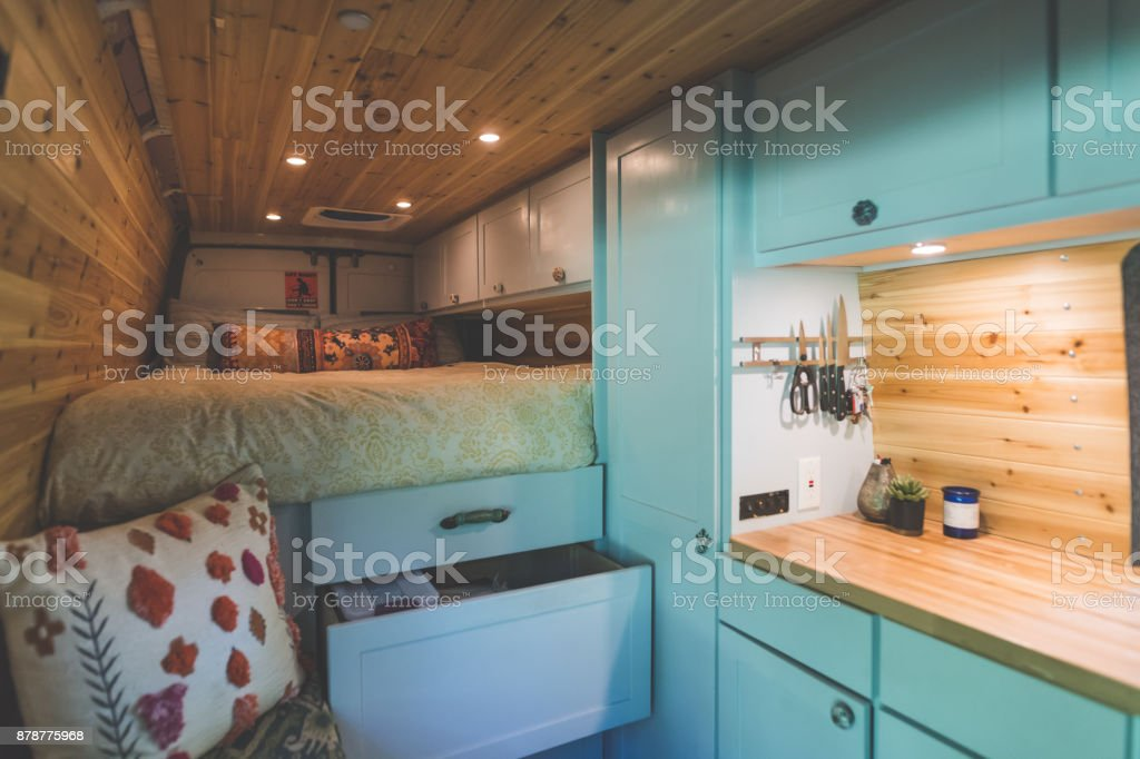 Living in a Van Living space of a young couple who live in a van. The sleeping area and bed are on the left. Underneath are cupboards and storage space. On the right are cabinets and a kitchen counter. The walls and ceilings are wood panels. Alternative Lifestyle Stock Photo