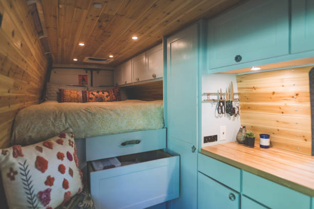 Living in a Van Living space of a young couple who live in a van. The sleeping area and bed are on the left. Underneath are cupboards and storage space. On the right are cabinets and a kitchen counter. The walls and ceilings are wood panels. rv interior stock pictures, royalty-free photos & images