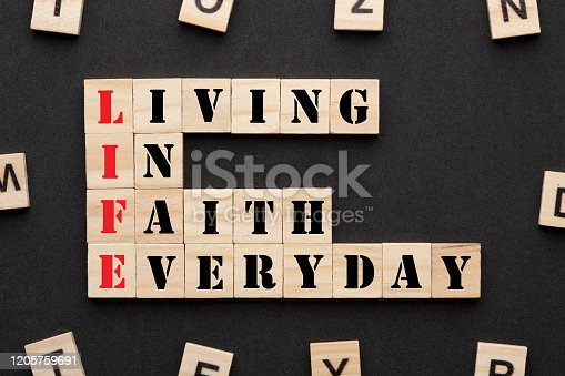 Living in faith everyday in wooden blocks on black background. Acronym Life