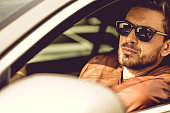 Handsome european man driving his luxury car and looking at the camera.