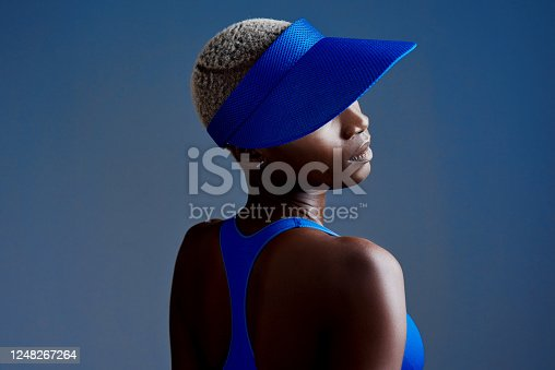 Studio shot of a sporty young woman wearing a visor while posing against a blue background