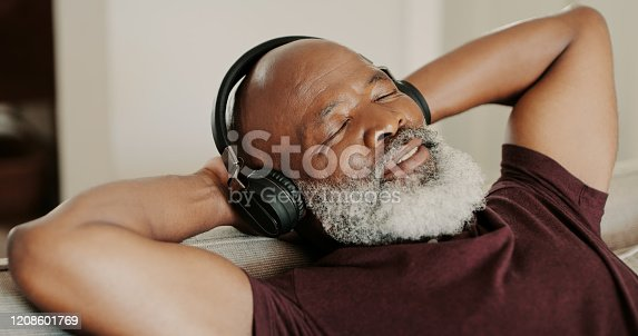 Cropped shot of a senior man sitting alone on his sofa and listening to music through headphones