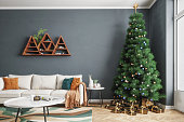 Large christmas tree and christmas presents in a modern living room.