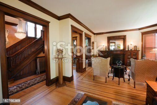 Subject: The living room of a renovated and restored Victorian style home interior with period furniture.