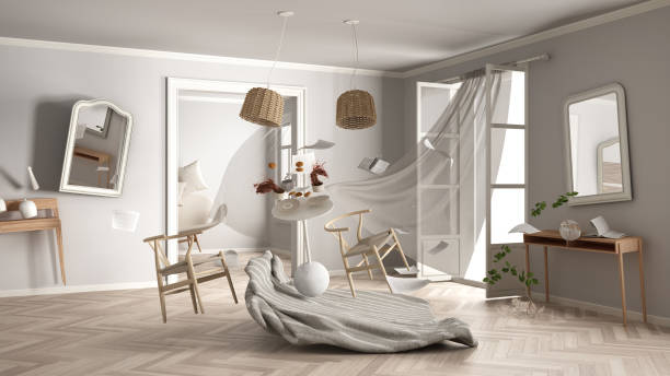 Living room, home chaos concept with chairs and table, carpet, windows and curtains, broken vase, mirrors, furniture and other accessories flying in the air, explosion, gust of wind stock photo