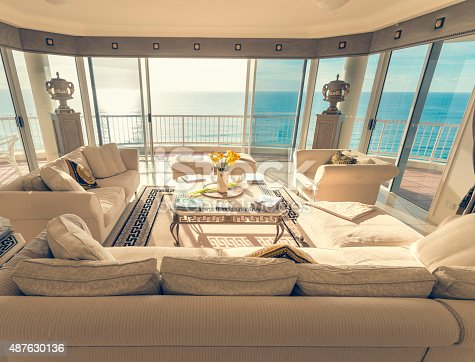 Living room in a luxury beachfront apartment with view. There is a magnificent view of the ocean from the floor to ceiling windows. The living room has a large sofa, coffee table and some flowers. Very spacious and luxurious.