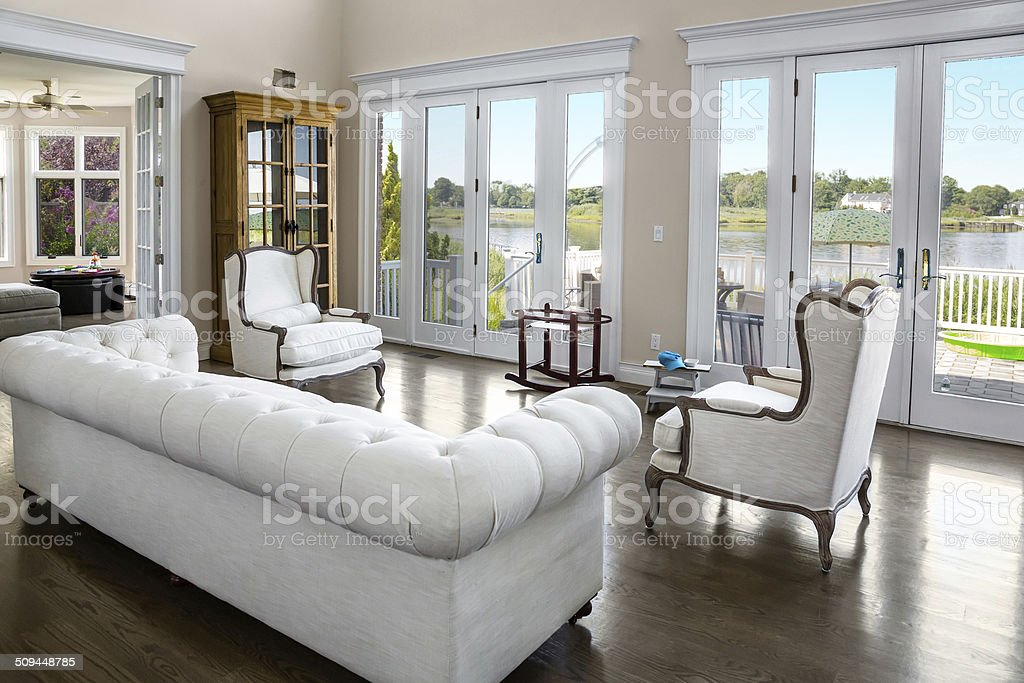 Living room in an elegant home with doors to lake stock photo