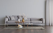 Living room interior with grey sofa and two coffee tables on the carpet. Empty gray wall mockup. A pile of books on the carpet, a candle and flowers on the table. 3D render. 3D illustration.