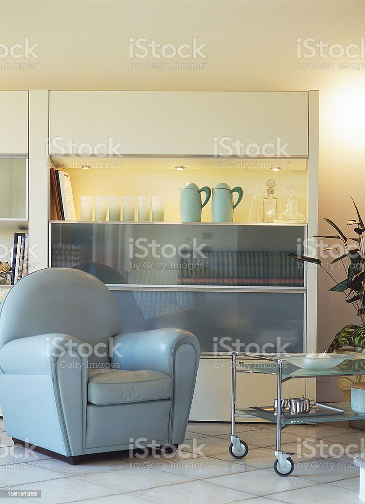 Living room: leather gray armchair, glass indoor trolley and shelf stock photo