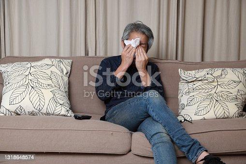 The senior Asian man sitting on the sofa in the livingroom.