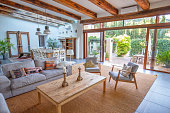 Elegant farmhouse living area with sofas and easy chairs and patio doors on to garden