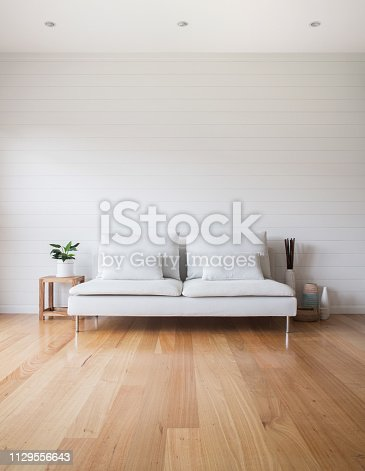 Stylish living room scene with white VJ panelling walls, white couch and timber floor. Lots of copy space.