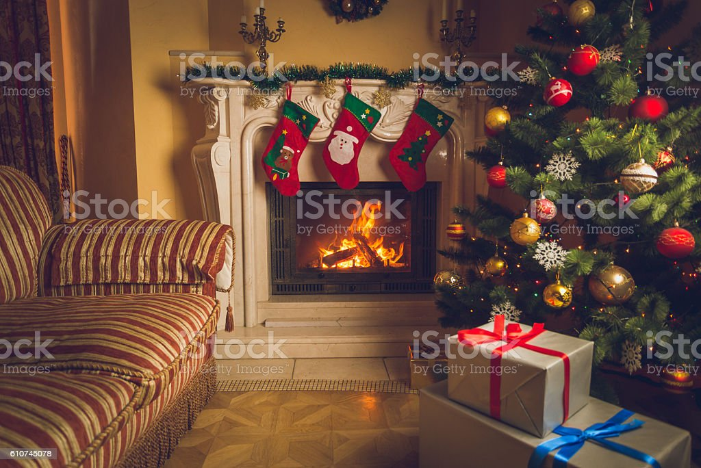 Living room with burning fireplace and decorated Christmas tree stock photo