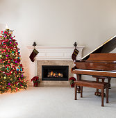 Living room with glowing fireplace, grand piano and decorated Christmas tree for the holidays
