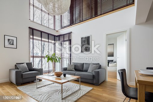 Living room with many, big windows with blinds and hardwood floor