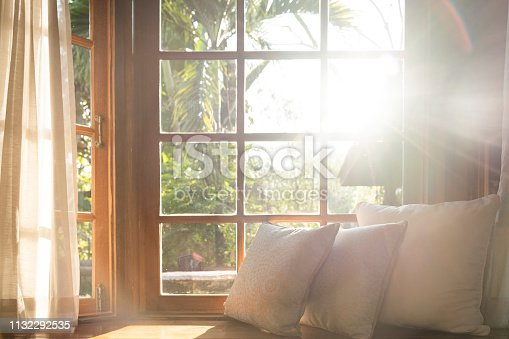 Living room with part of sofa in sunny day and white cushion interior background concept.