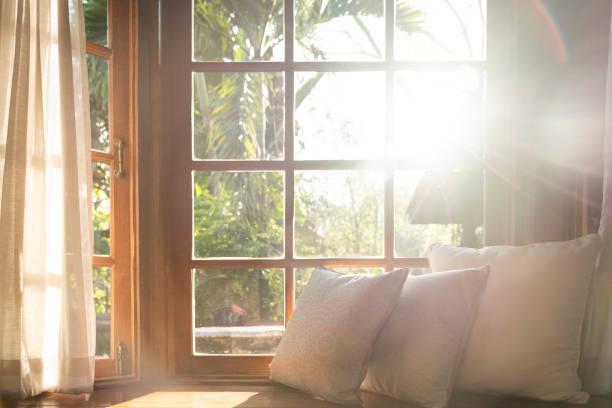 salon z częścią sofy w słoneczny dzień i białą zasłoną. - okno zdjęcia i obrazy z banku zdjęć