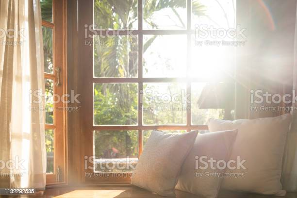 Photo of Living room with part of sofa in sunny day and white curtain.