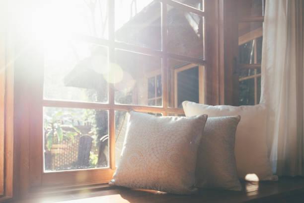 Wohnzimmer mit einem Teil des Sofas am sonnigen Tag und weißer Vorhang. – Foto