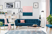 Modern living room interior with blue sofa and rug, art collection and pink details