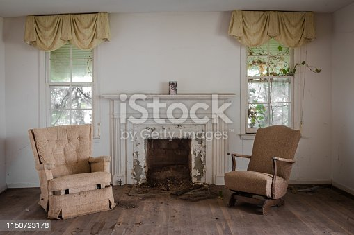 Living room with two chairs with a fireplace in an abandoned home during the day
