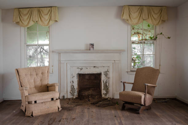 Living room with two chairs with a fireplace in an abandoned home Living room with two chairs with a fireplace in an abandoned home during the day run down stock pictures, royalty-free photos & images