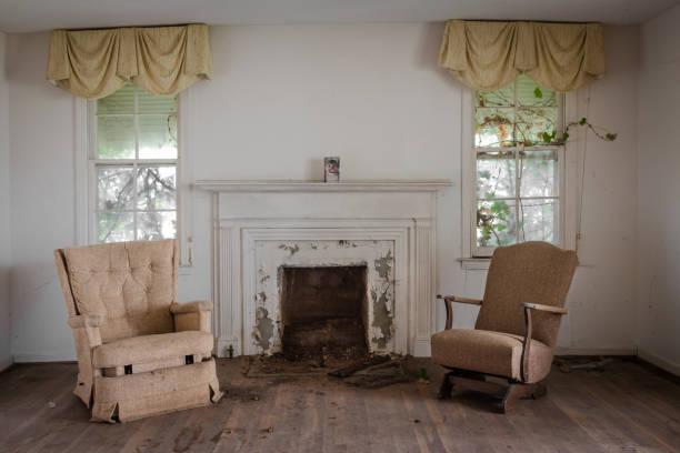 woonkamer met twee stoelen met open haard in een verlaten huis - slechte staat stockfoto's en -beelden