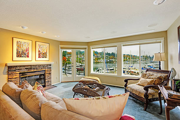Living room with water front view Living room with walkout deck and water front view. Furnished with antique sofa and chair. Gig Harbor. gig harbor stock pictures, royalty-free photos & images