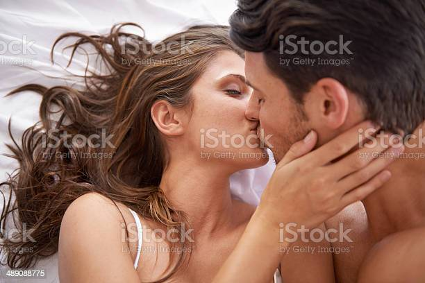 Shot of an affectionate young couple kissing in bed
