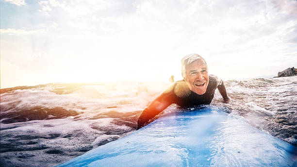 Living to the fullest Active and happy senior man living to the fullest, surfing on a surfboard during his summer vacation  leisure equipment stock pictures, royalty-free photos & images
