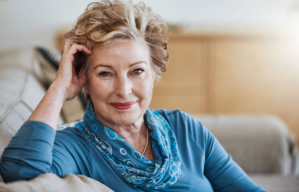Living well, aging well Portrait of an attractive senior woman relaxing on the sofa at home one mature woman only stock pictures, royalty-free photos & images