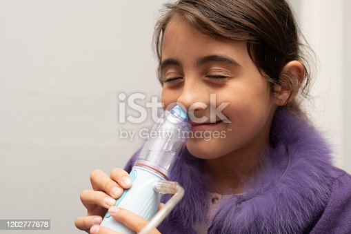 Living with allergies. Cold and flu. Making aerosol. Little girl with cold  doing aerosol.
