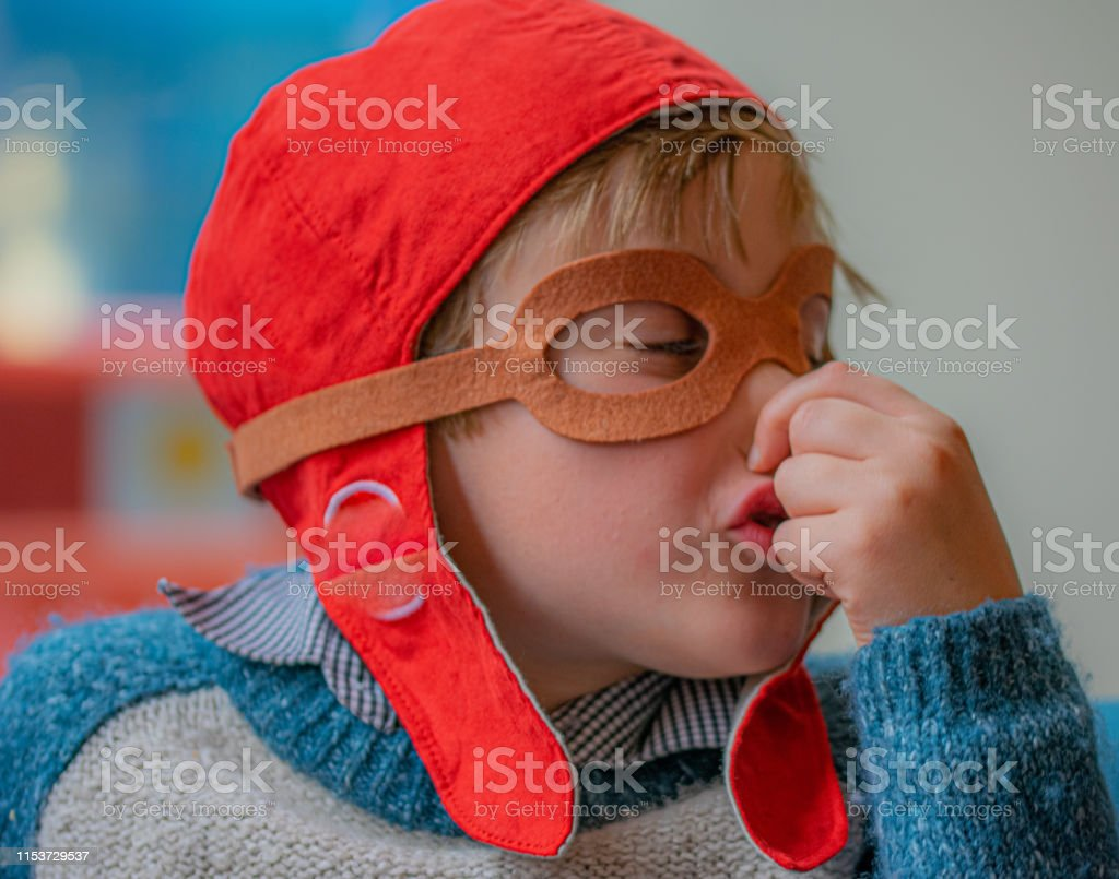 Living with allergies. Young boy sneezing and rubbing his nose, wearing a red pilot cap. Allergy Stock Photo