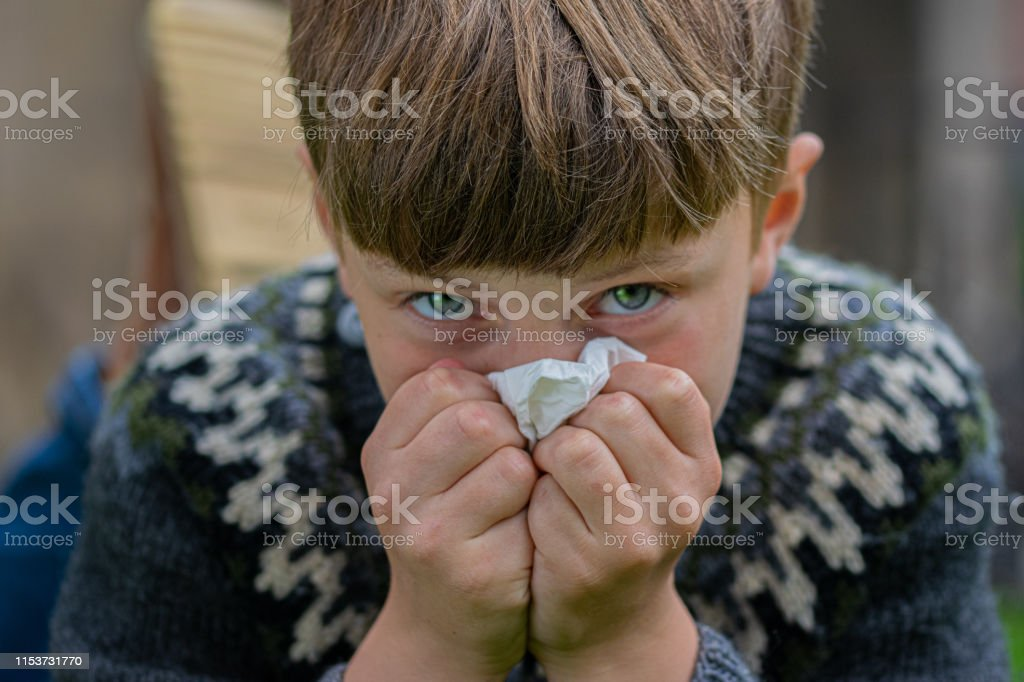 Boy lying down and blowing his nose with a tissue.