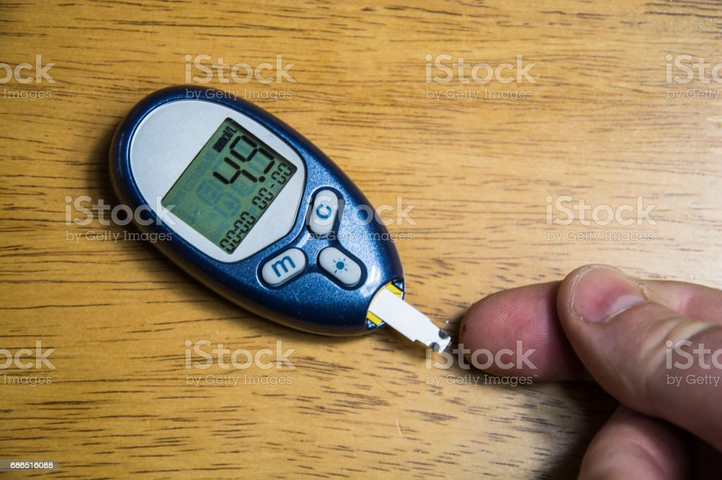 Living with and managing life with diabetes. Pricked finger being held towards a blood glucose monitor royalty free stockfoto