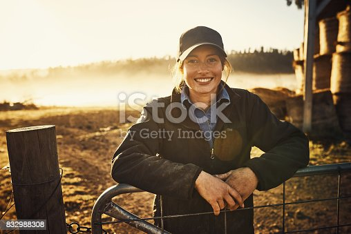 Portrait of a young woman leaning against a gate on a farm