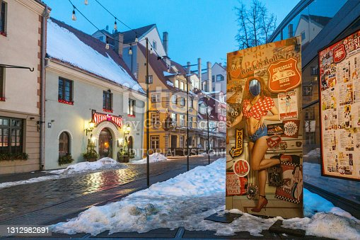 Riga, Latvia - February 22, 2021: Livu square amidst the COVID-19 pandemic in winter. A colorful bar advertisement can be seen in the foreground. And a steak restaurant in the background. Both were closed because of emergency situation in Latvia