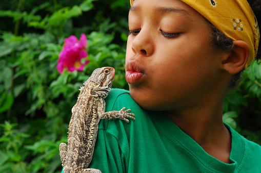 Lizard perched on boy's shoulder in tropical garden