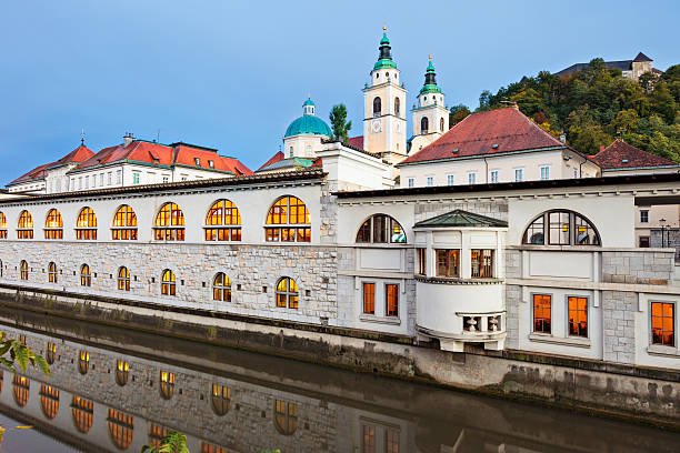 Ljubljana, Slovenia The landmark Central Market and Saint Nicholas Cathedral on the banks of the Ljubljanica River with the Ljubljana Castle in the background. ljubljana castle stock pictures, royalty-free photos & images