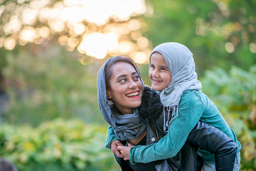 A beautiful Muslim mother is giving her daughter a piggy back while outdoors at the park. They are both happy and smiling.