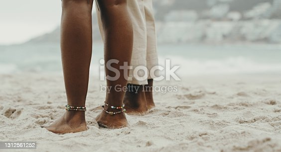 Closeup front view of unrecognizable woman walking on a beach while seawater is splashing on her feet. Shot in a low sunset light.