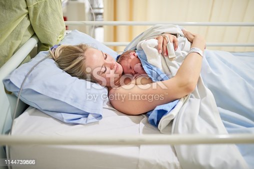 Shot of a beautiful young mother lying in bed with her newly born baby girl in the hospital