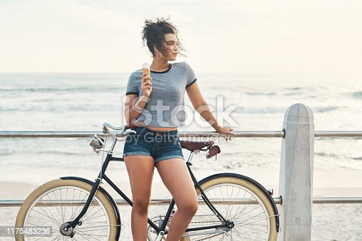 Shot of a beautiful young woman out on the promenade with her bicycle