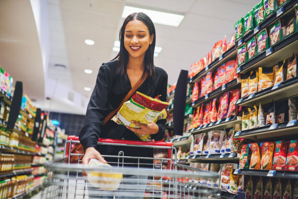 I'll definitely be shopping here again Shot of a young woman shopping in a grocery store snack aisle stock pictures, royalty-free photos & images