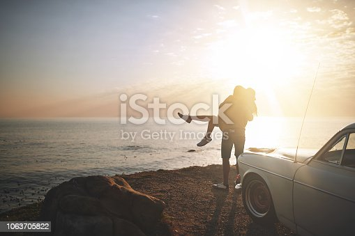 Shot of a young couple making a stop at the beach while out on a road trip