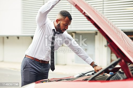 Shot of a man checking under the hood of his car after breaking down