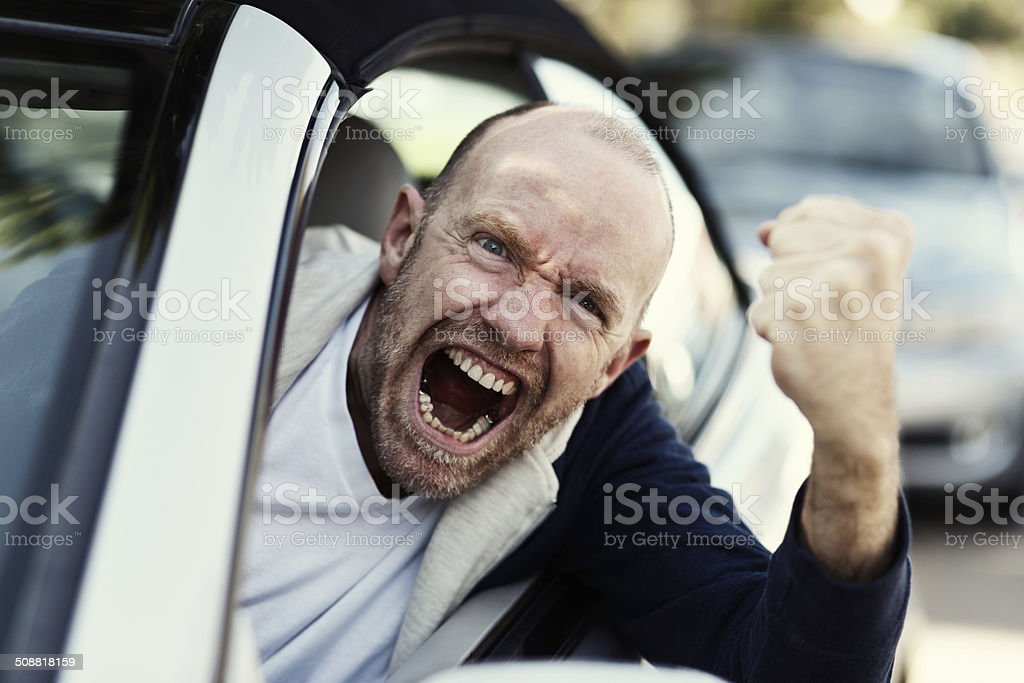 I'll get you! Frightening male driver shakes fist threateningly stock photo