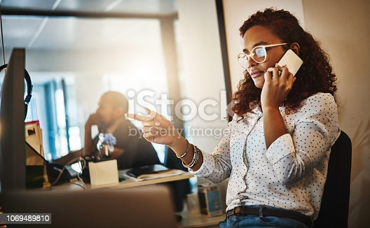 Shot of a young businesswoman using a mobile phone and computer during a late night at work