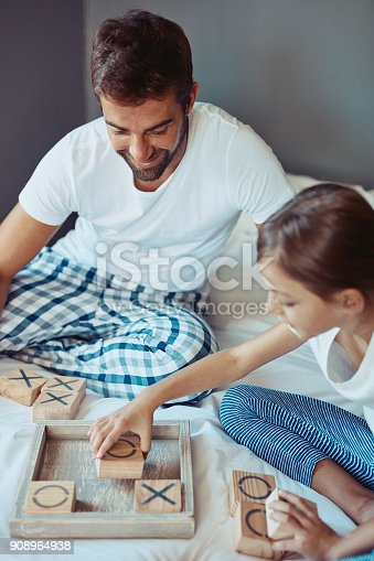 Shot of a man playing a board game with his little girl at home